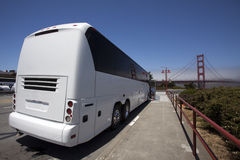 White Tour Charter Bus at Golden Gate Bridge. Rear and side view of white tour charter bus parked at San Francisco's Golden Gate Bridge Stock Photography