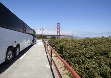 White Tour Charter Bus at Golden Gate Bridge. Rear and side view of white tour charter bus parked at San Francisco's Golden Gate Bridge Stock Image