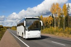 white tourist bus on autumn country highway. Tourist bus, autumn, highway Scandinavia Stock Photos