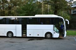 White tourist bus for excursions. The bus is parked in a parking lot near the park.  royalty free stock image