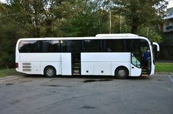 White tourist bus for excursions. The bus is parked in a parking lot near the park.  stock photography
