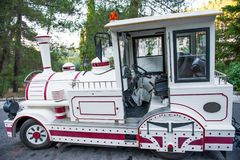 White tourist transport in the form of a toy train. Fun transport stock photo