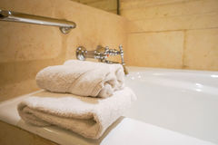 White towel on bathtub in hotel bathroom stock image