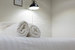 White towel on bed in guest room for hotel customer Royalty Free Stock Images