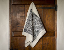 White Towel with Black Bird's Eye Pattern Hanging on  Door. A white linen or towel with printed black  bird's eye pattern and lines hanging on a shut wooden door Royalty Free Stock Images