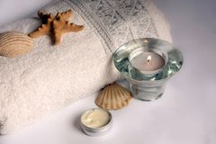A white towel, candle and massage cream Stock Image