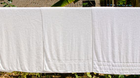 White towel on clothesline in sunny day Stock Image