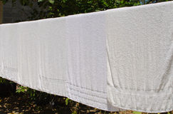 White towel on clothesline in sunny day Royalty Free Stock Image