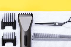On white towel electric hair clipper and hairdresser scissors stock images