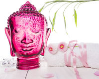 White towel with flowers and  head of glass Buddha Stock Photos