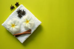 White towel with flowers of plumeria with stars of anise and cinnamon sticks on the yellow background. Stock Photography