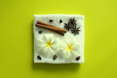 White towel with flowers of plumeria with stars of anise and cinnamon sticks on the yellow background. Stock Photo