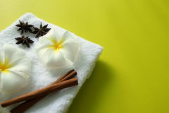 White towel with flowers of plumeria with stars of anise and cinnamon sticks on the yellow background. Stock Image