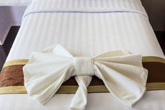 White Towel folded in bow shape on bed Royalty Free Stock Photo