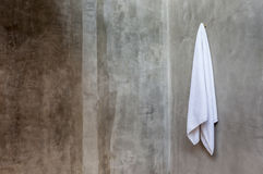 White towel is hanging on the exposed concrete wall in the bathr Royalty Free Stock Photos