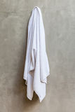 White towel is hanging on the exposed concrete wall in the bathr Stock Photo