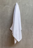 The white towel is hanging on a hanger with concrete wall in the Stock Images