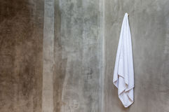 The white towel is hanging on a hanger with concrete wall in the. Clean and white towel is hanging on a hanger with concrete wall in the bathroom Stock Photo