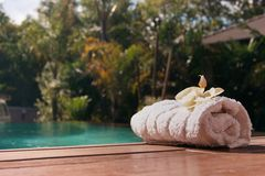 White towel near the pool with palm trees Royalty Free Stock Photos