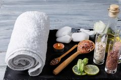 White towel, pebbles and aroma oil for spa procedures on a dark surface. White bath towel, various pebbles of different shapes and aroma massage oil for spa Stock Images
