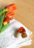 White towel and scattered pebbles. Decorated with a orange tulips and red carnation, suitable for spa and healthcare setting Royalty Free Stock Images