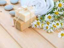 White towel, soap bars and camomile bouquet on the natural wood Royalty Free Stock Image