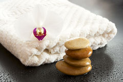 White towel with stones and orchids. Royalty Free Stock Photos