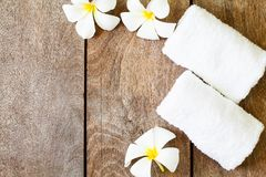 White towel with white flower on vintage wooden background royalty free stock image