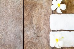 White towel with white flower on vintage wooden background royalty free stock images