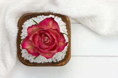 White towel and wooden bowl filled with bath salt Stock Image