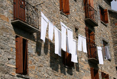 White towels. Hanging on a line to dry in front of a stone house Royalty Free Stock Images