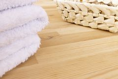 White towels and basket with spicy dry plants on a light wooden background royalty free stock photography