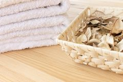 White towels and basket with spicy dry plants on a light wooden background stock image