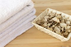 White towels and basket with spicy dry plants on a light wooden background stock photography