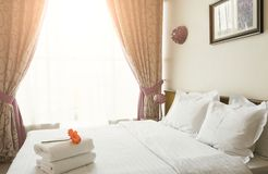 White towels on bed in hotel bedroom Stock Image