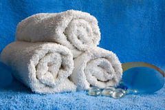 White towels on a blue background. White towels and pebbles on a blue background Royalty Free Stock Photography