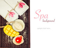 White towels, flowers and mango coconat shape soap. White towels, flowers and mango coconut shape soap on bamboo mat. Isolated. Tropical spa, relax, vacation Royalty Free Stock Photography