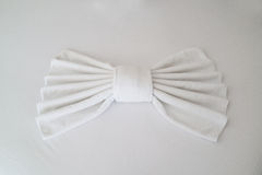 White towels folded into a bow shape. Lying on the white bed sheet Royalty Free Stock Photos