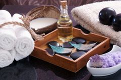 White towels knitted next to the set for massage from Bian stones, aroma oil and violet salt, in a wooden box a set of Royalty Free Stock Photos