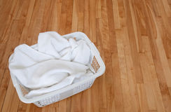 White towels in a laundry basket on wooden floor Stock Photos