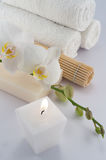 White towels, orchid and candle. White towels and soap, orchid, candle on white bacground stock images