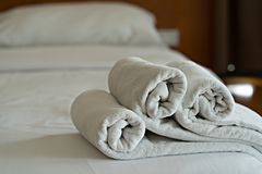 White towels roll on bed in hotel bedroom royalty free stock photo