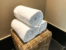 White towels rolled into a roll in the spa on a wicker cabinet on a beige background. 