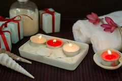 White towels, seashells and candles in sand with gift boxes Royalty Free Stock Photo