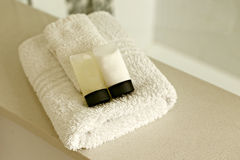 White towels with shampoo and conditioner. In a hotel. Space to add own design or name on the shampoo and conditioner bottles Stock Images