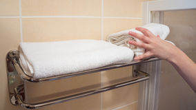 White towels takes the human hand. White takes the human hand towels in the bathroom stock photos