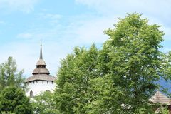 Tower of church in open-air museum. White tower of church with shingles roof behind trees in open-air museum Liptov Village Museum Pribylina in Slovakia Royalty Free Stock Image