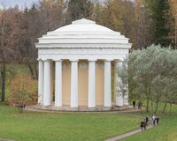 A white tower in the park and walking people. Autumn trees on the background Royalty Free Stock Photos