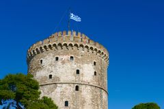 The White Tower in Thessaloniki. With waving Greek flag, Greece stock photo