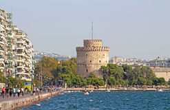 White Tower and unidentified people are walking on the embankment in Thessaloniki, Greece Royalty Free Stock Photography
